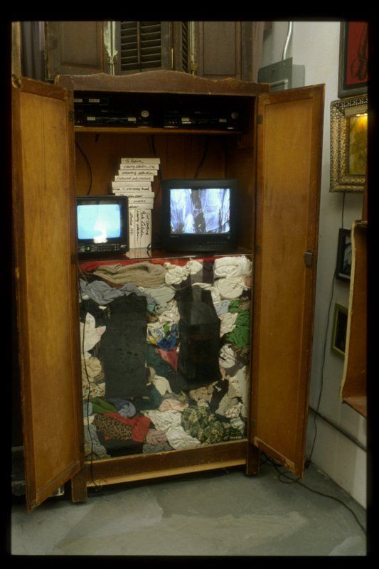 Cut clothing wardrobe. 2000; remants from cut clothing performance (1997), wooden cabinet, glass, videos, monitors, etc.
