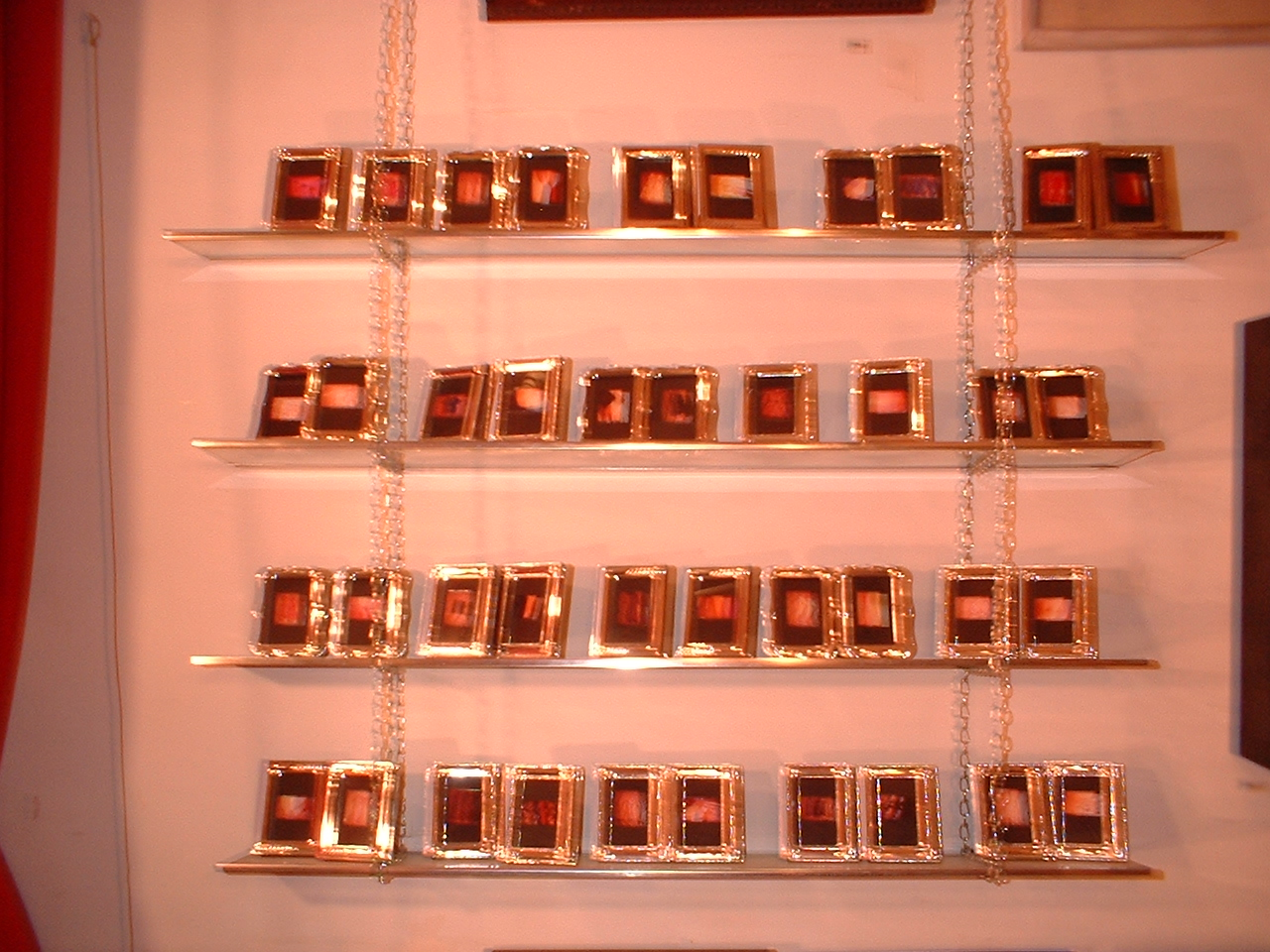 Poetry of cut clothing. 1999; color photographs, metal frames w/ glass, glass & metal shelves, chain