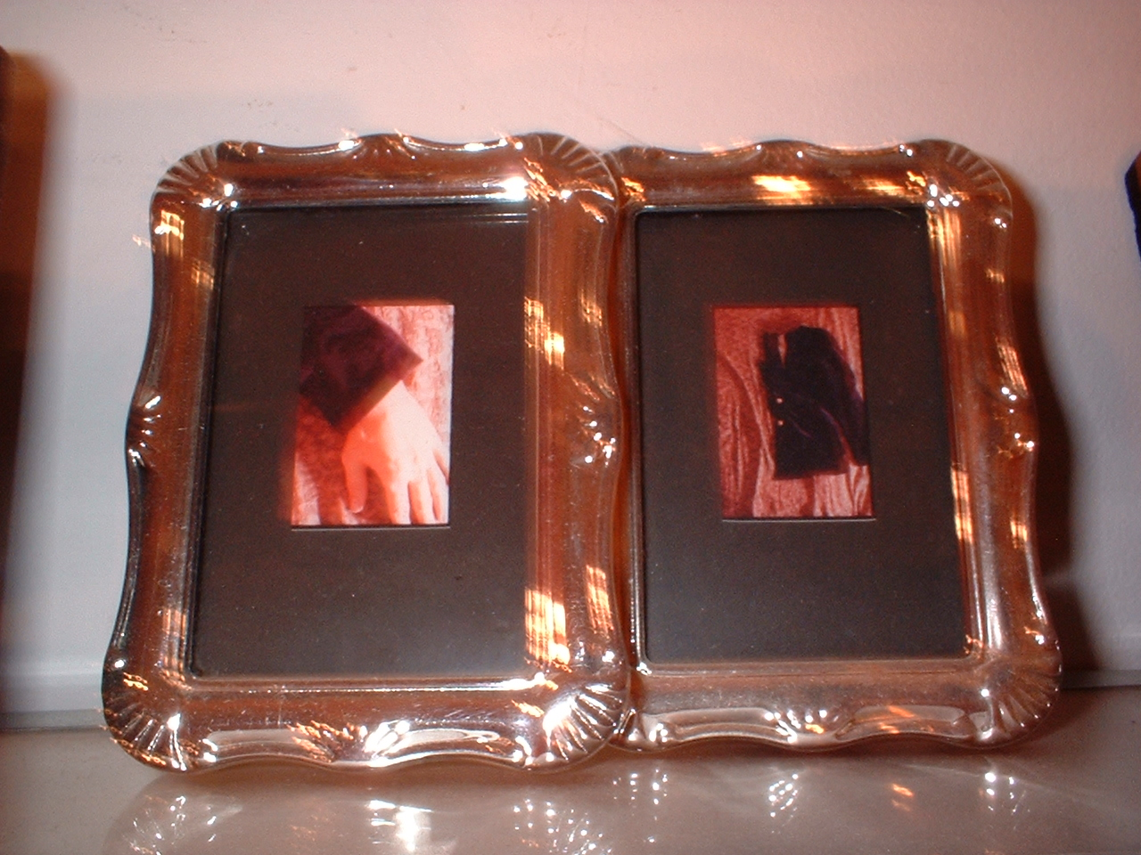 [detail] Poetry of cut clothing. 1999; color photographs, metal frames w/ glass, glass & metal shelves, chain